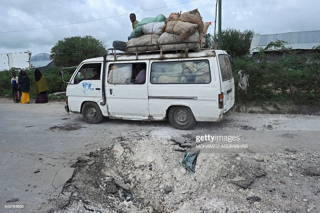This picture taken on June 30, 2016, in Afgooye shows the bomb crater on the site where a minibus exploded on a landmine. A roadside bomb ripped apart a minibus just outside Somalia's capital Mogadishu on Thursday, killing at least eight people and injuring several others, a witness said. 'There was a terrible incident, a landmine hit a civilian minibus,' said Mohamed Wedow, a witness at the scene near the town of Afgooye. 'At least eight people died and more than 20 others were wounded in the blast.' ABDIWAHAB