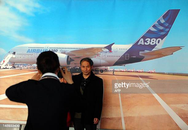 This picture taken on June 7 shows a Chinese air passenger getting his photo taken by a poster of the Airbus A380 at the airport in Wuhan central...