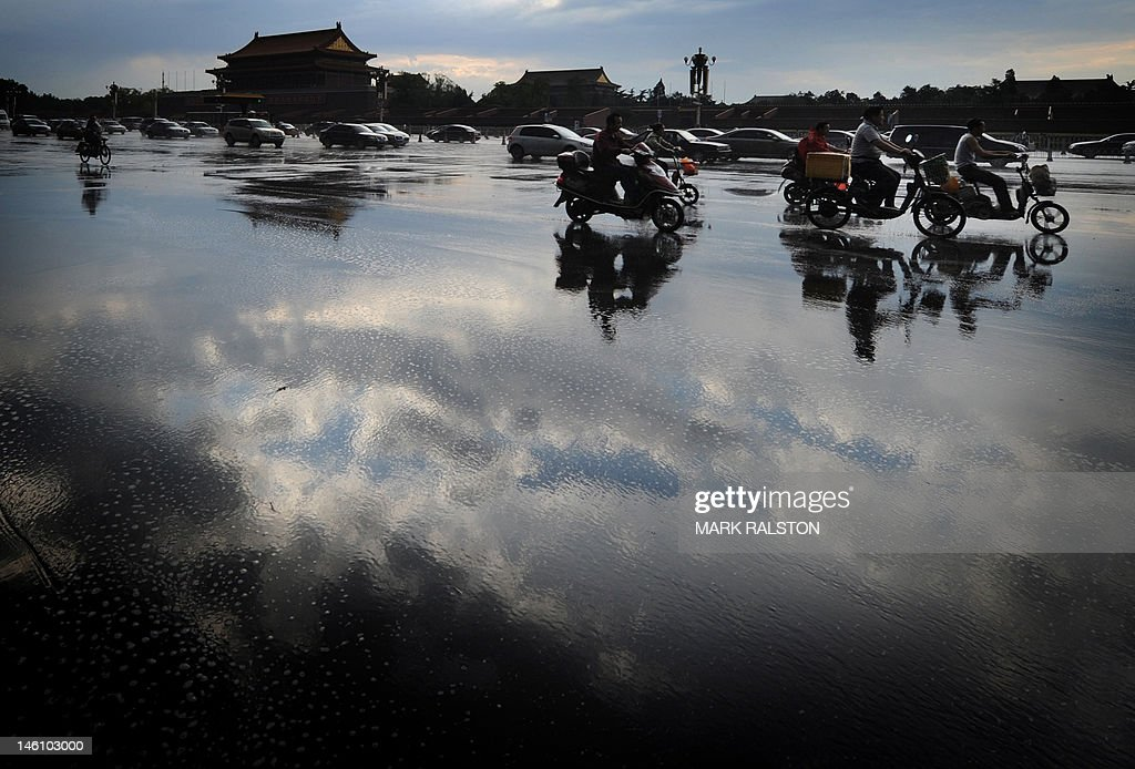 This picture taken on June 9, 2012 shows Chinese commuters traveling past the Tiananmen Gate in Beijing. China said its exports and imports shot up in May, but analysts cautioned the better-than-expected data was no cause for joy amid global economic woes and a slowdown in the Asian powerhouse. AFP PHOTO/Mark RALSTON
