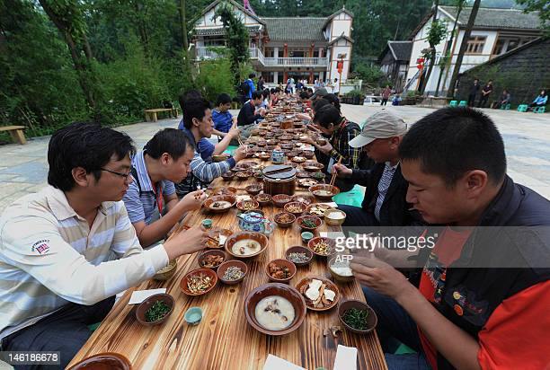 This picture taken on June 9 shows visitors enjoying a meal in Qingyanguzhen located in the southern suburbs of Guiyang southwest China's Guizhou...