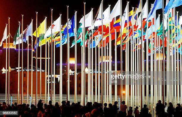 This picture taken on late May 2 2010 shows visitors standing next to flags of the participating nations at the site of the World Expo 2010 in...