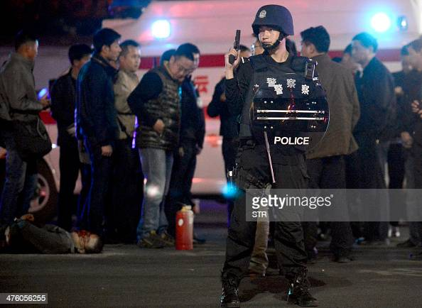 This picture taken on March 1 2014 show Chinese policemen standing over a body of one of the alleged attackers at the railway station in Kunming...