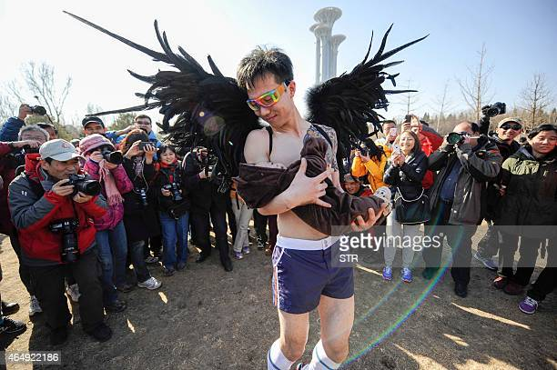 This picture taken on March 1 2015 shows a participant posing for photos in the 'HalfNaked Marathon' at a park in Beijing Hundreds of runners joined...
