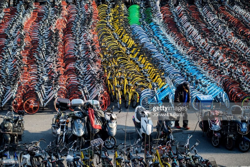 This picture taken on March 1, 2017 shows impounded bicycles from the bike-sharing schemes Mobike and Ofo in Shanghai. Shanghai has impounded thousands of brightly coloured bikes placed on city streets by cycle-sharing companies, in the latest sign of impatience with an explosion of the haphazardly-parked two-wheelers. / AFP PHOTO / Johannes EISELE