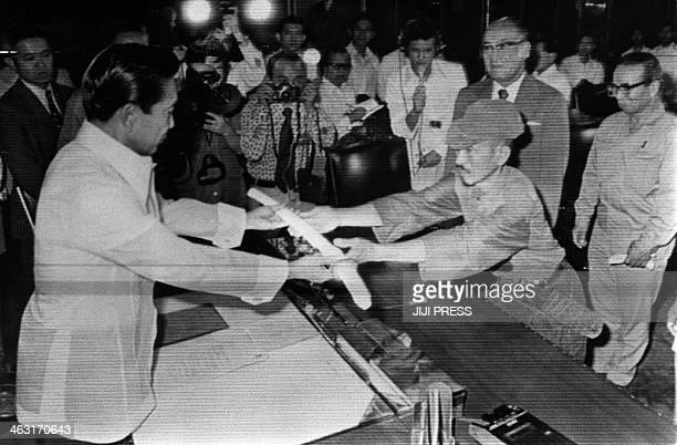 This picture taken on March 11 1974 shows former Japanese imperial army soldier Hiroo Onoda offering his military sword to former Philippine...
