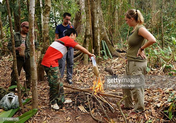 This picture taken on March 12 2011 shows Briton Joe Part and his girlfriend Emily Soyer watching local Khmu hilltribe ethnic guides cooking a soup...