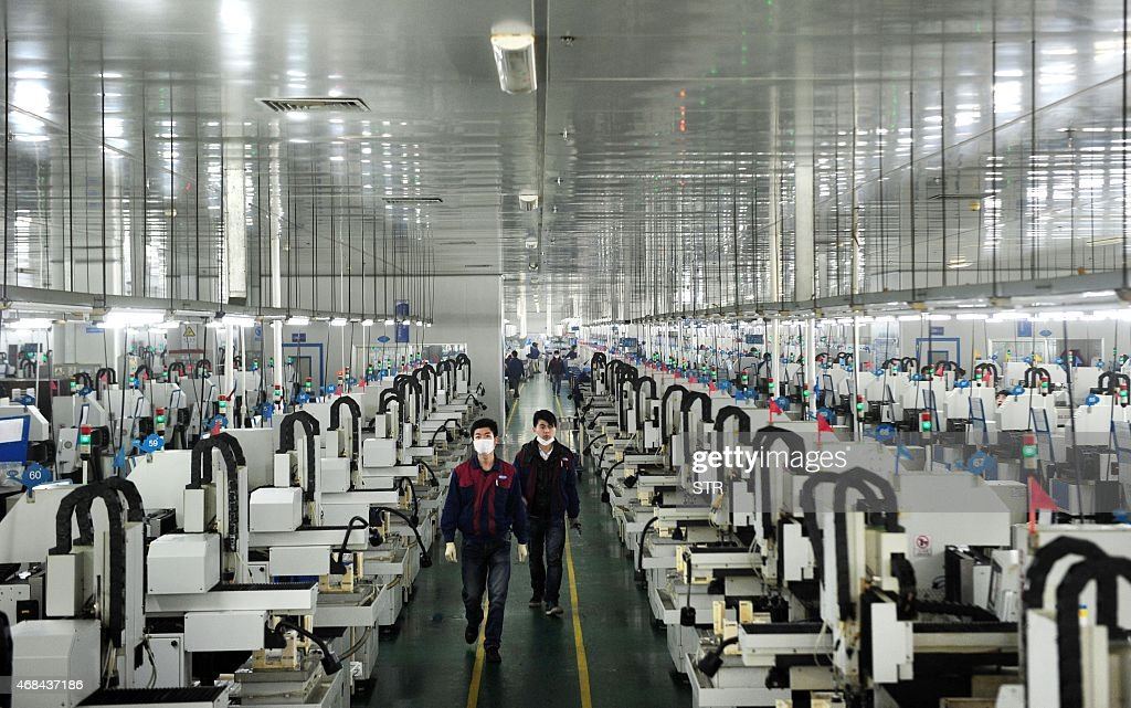 This picture taken on March 12 2015 shows employees working in the workshop of Lens Technology in Liuyang central China's Hunan province Zhou Qunshu...