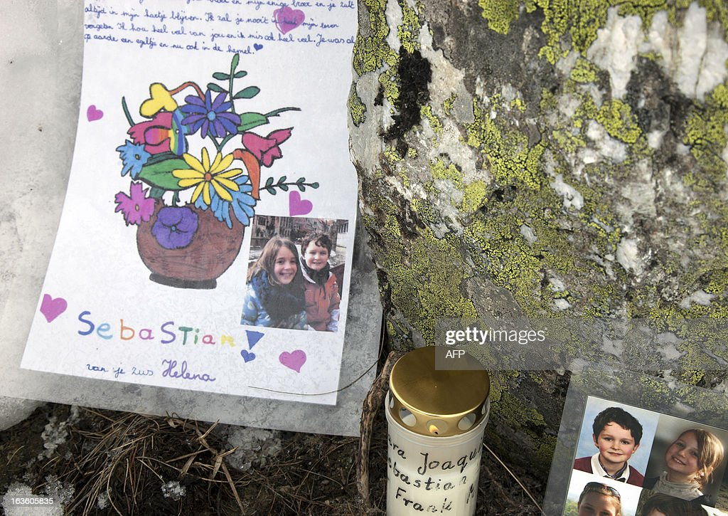 This picture taken on March 13, 2013 above Saint-Luc, in the Swiss canton of Valais, shows drawings, pictures, and a candle lying under a commemorative plaque bearing the name of the persons who died in a traffic accident a year ago. A ceremony in memory of the 22 Belgian school children and six adults killed in a horrific bus accident in the Swiss Alps will take place on the one-year anniversary of the tragedy near the accident site. The small town of Sierre in the southern canton of Valais announced on its website on February 21 that it would host the ceremony at 6:00 pm (1700 GMT) on March 13 at the town church, a year after the Belgian bus smashed into the wall of a nearby Alpine tunnel at 100 kilometres (65 miles) an hour.