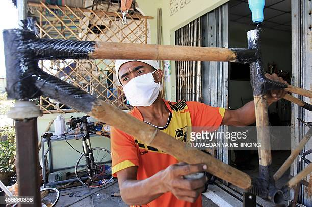 This picture taken on March 13 2015 shows Thai craftsman Sanit Tuanjolong hanging an assembled bamboomade bicycle frame before attaching to it the...