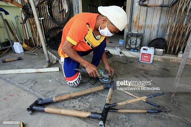 This picture taken on March 13 2015 shows Thai craftsman Sanit Tuanjolong as he smoothes the edges of a piece of an assembled bamboomade bicycle...