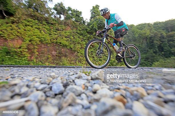 This picture taken on March 14 2015 shows Thai craftsman Sanit Tuanjolong riding a handmade bambooframe bicycle on a mountain road in Yala province...