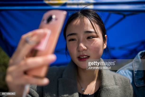 This picture taken on March 14 2017 shows Jiang Mengna live broadcasting during a break at the Yiwu Industrial Commercial College in Yiwu east...