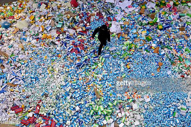 This picture taken on March 14 shows a Chinese policeman walking across a pile of fake medicines seized in Beijing in recent months which were later...