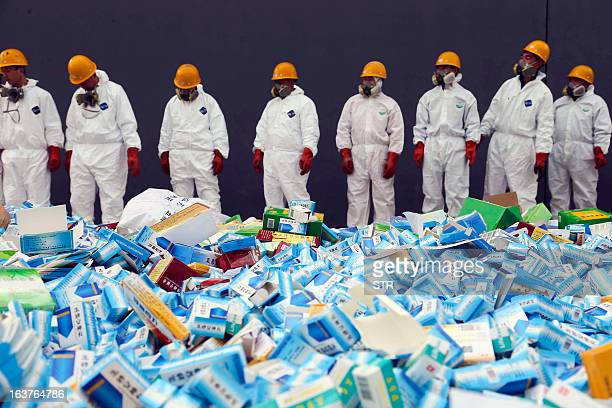 This picture taken on March 14 shows health workers preparing to destroy fake medicines seized in Beijing in recent months The rapid growth of...