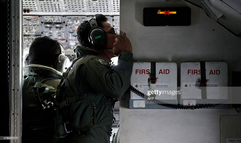 This picture taken on March 15, 2014 shows crew member from a Malaysian Air Force CN235 aircraft working during a search and rescue (SAR) operation to find the missing Malaysia Airlines flight MH370 plane over the Strait of Malacca. The disappearance of a Malaysia Airlines passenger jet is a potential disaster for a national flag carrier already struggling to cauterise severe financial hemorrhaging in the face of intensifying industry competition, raising the spectre of costly lawsuits and a drop in bookinngs.