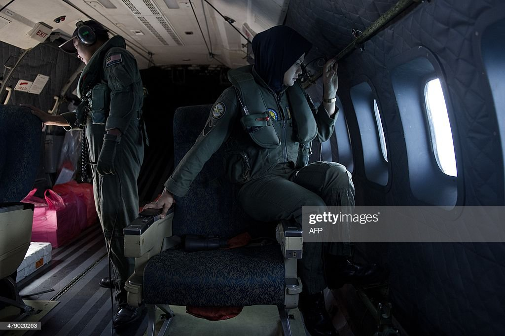 This picture taken on March 15, 2014 shows crew members looking outside windows from a Malaysian Air Force CN235 aircraft working during a search and rescue (SAR) operation to find the missing Malaysia Airlines flight MH370 plane over the Strait of Malacca. The disappearance of a Malaysia Airlines passenger jet is a potential disaster for a national flag carrier already struggling to cauterise severe financial hemorrhaging in the face of intensifying industry competition, raising the spectre of costly lawsuits and a drop in bookinngs.