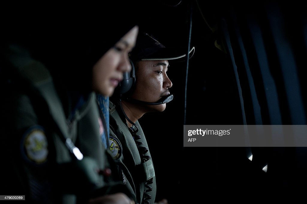 This picture taken on March 15, 2014 shows crew members looking outside windows from a Malaysian Air Force CN235 aircraft working during a search and rescue (SAR) operation to find the missing Malaysia Airlines flight MH370 plane over the Strait of Malacca. The disappearance of a Malaysia Airlines passenger jet is a potential disaster for a national flag carrier already struggling to cauterise severe financial hemorrhaging in the face of intensifying industry competition, raising the spectre of costly lawsuits and a drop in bookinngs. AFP PHOTO / MOHD RASFAN