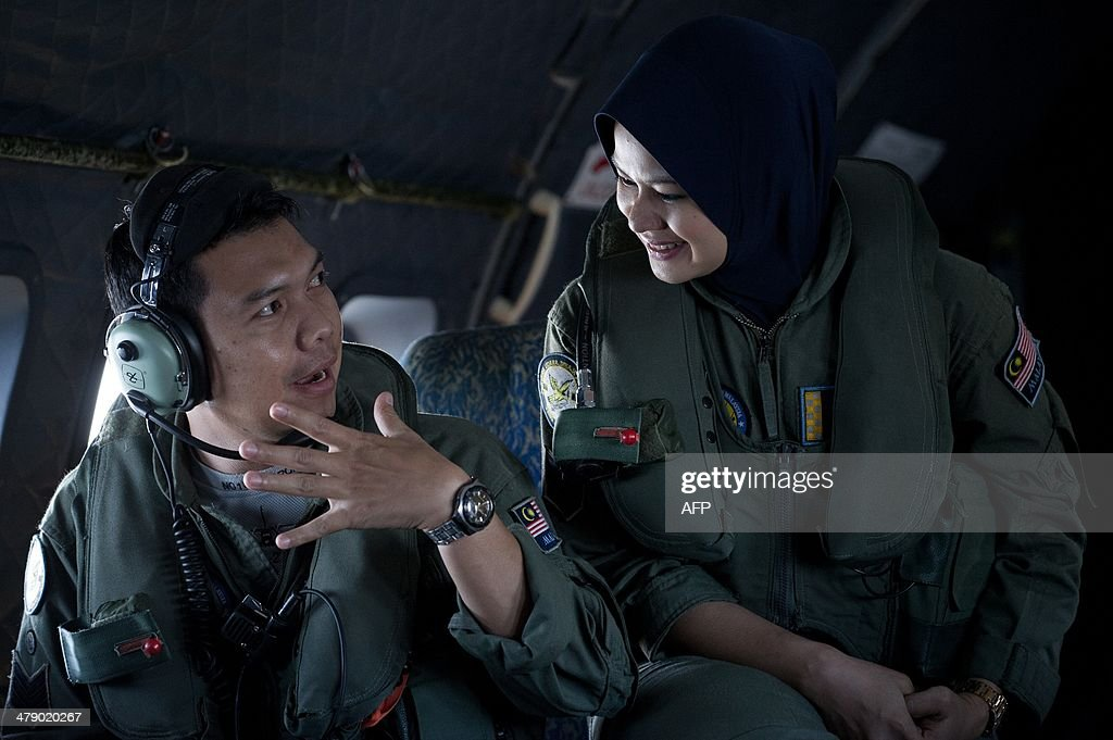 This picture taken on March 15, 2014 shows crew members talking to each others onboard a Malaysian Air Force CN235 aircraft working during a search and rescue (SAR) operation to find the missing Malaysia Airlines flight MH370 plane over the Strait of Malacca. The disappearance of a Malaysia Airlines passenger jet is a potential disaster for a national flag carrier already struggling to cauterise severe financial hemorrhaging in the face of intensifying industry competition, raising the spectre of costly lawsuits and a drop in bookinngs.