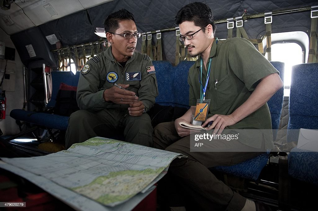 This picture taken on March 15, 2014 shows Royal Malaysian Air Force Navigator captain Izam Fareq Hassan (L) explaning to Agence France-Presse correspondent Shannon Teoh on board a Malaysian Air Force CN235 during a search and rescue (SAR) operation to find the missing Malaysia Airlines flight MH370 plane over the Strait of Malacca. The disappearance of a Malaysia Airlines passenger jet is a potential disaster for a national flag carrier already struggling to cauterise severe financial hemorrhaging in the face of intensifying industry competition, raising the spectre of costly lawsuits and a drop in bookinngs.