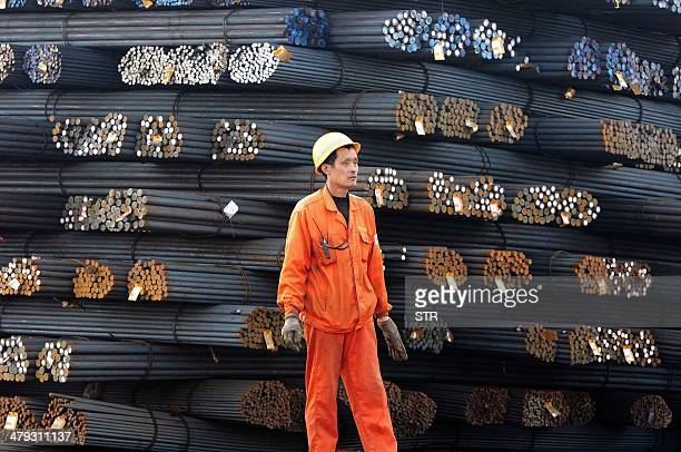 This picture taken on March 17 2014 shows a worker walking on steel rods in a steel market in Qingdao in eastern China's Shandong province Foreign...