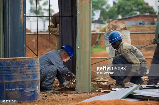 This picture taken on March 17 2014 shows workers at the construction site of the Kigali Conference Centre currently being built in the Rwandan...
