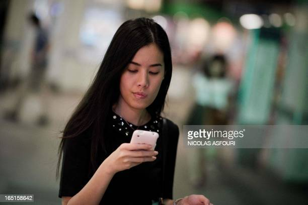 This picture taken on March 19 2013 shows a woman looking at her smartphone while walking at a BTS train station in Bangkok A recent...