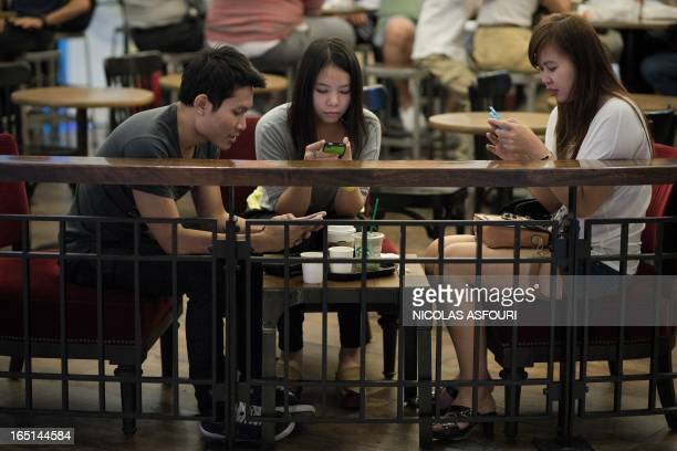 This picture taken on March 19 2013 shows friends looking at their smartphones at a coffee shop in a shopping mall in Bangkok A recent...