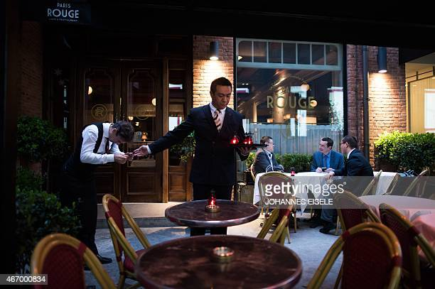 This picture taken on March 19 2015 shows a waiter preparing tables for the Goût de France event at the 'Paris Rouge' in Shanghai The 'Goût de...