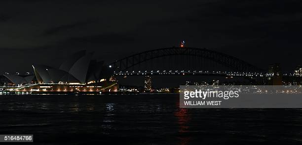 This picture taken on March 19 2016 shows Australia's iconic Sydney Opera House and Harbour Bridge with the lights turned off during the Earth Hour...