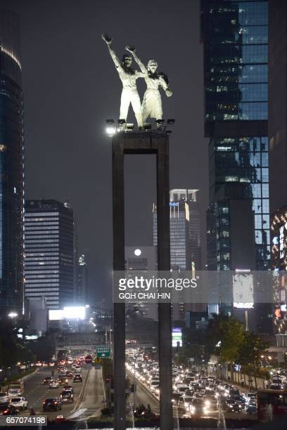 This picture taken on March 2 2017 shows the iconic Selamat Datang Monument which is also known as the Monument Bundaran HI lights up at night adding...
