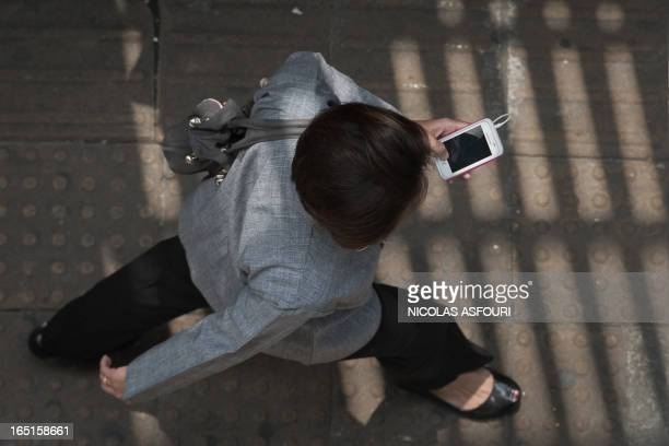 This picture taken on March 20 2013 shows a woman looking at her smartphone while walking in a street in Bangkok A recent Facebooksponsored study...