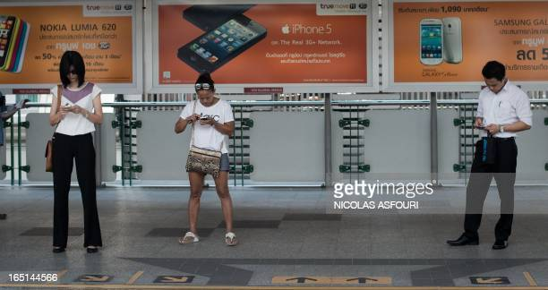 This picture taken on March 20 2013 shows people looking at their smartphones while waiting for a train at a BTS station in Bangkok A recent...
