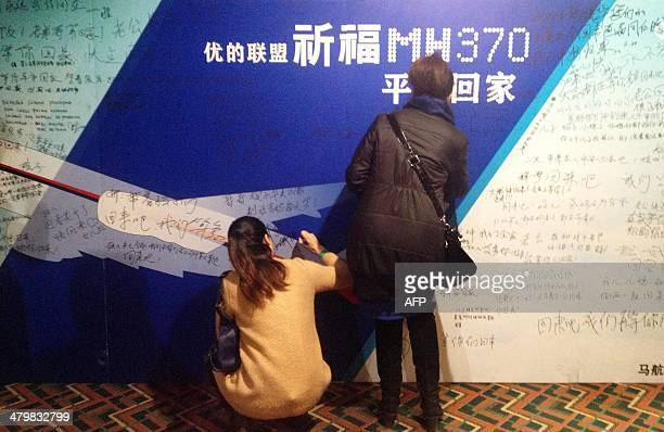 This picture taken on March 20 2014 shows relatives writing messages to missing passengers on a prayer board in the meeting room of Lido hotel where...