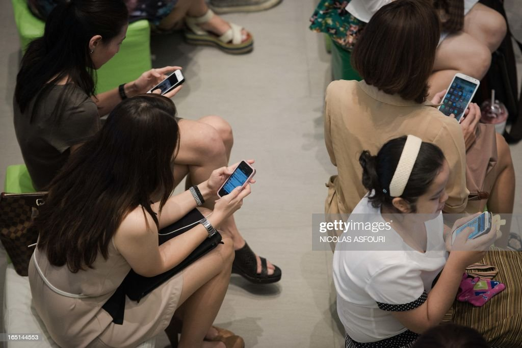 This picture taken on March 21, 2013 shows a group of people sitting down using their smartphones at a shopping mall in Bangkok. A recent Facebook-sponsored study showed smartphone owners are often connected all day. People can be found glued to their smartphones at airports, on trains, in restaurants and even while walking on the street, creating a disconnection from their immediate surroundings. Smartphone sales are expected to continue to surge in 2013 with some 918 million units to be bought worldwide. AFP PHOTO / Nicolas ASFOURI