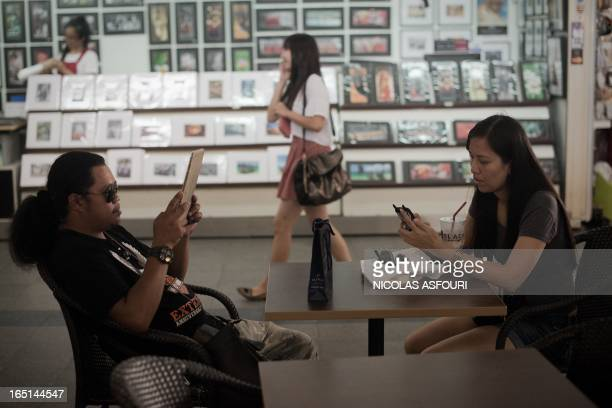 This picture taken on March 21 2013 shows a man using a tablet and a woman using a smartphone as another young woman passes by talking on a...