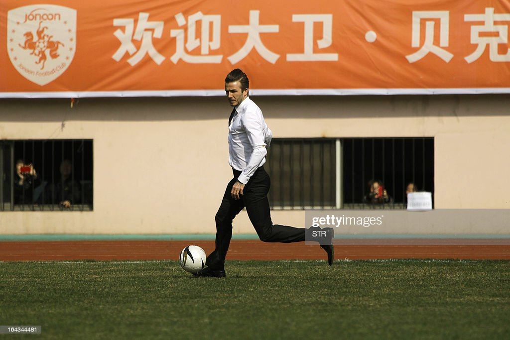 This picture taken on March 22, 2013 shows football superstar David Beckham playing football with young Chinese players in Tiantai Stadium in Qingdao, east China's Shandong province. Beckham raised the prospect of one last stop on his global football journey on March 20, refusing to rule out playing in China after his contract with Paris Saint-Germain ends. CHINA