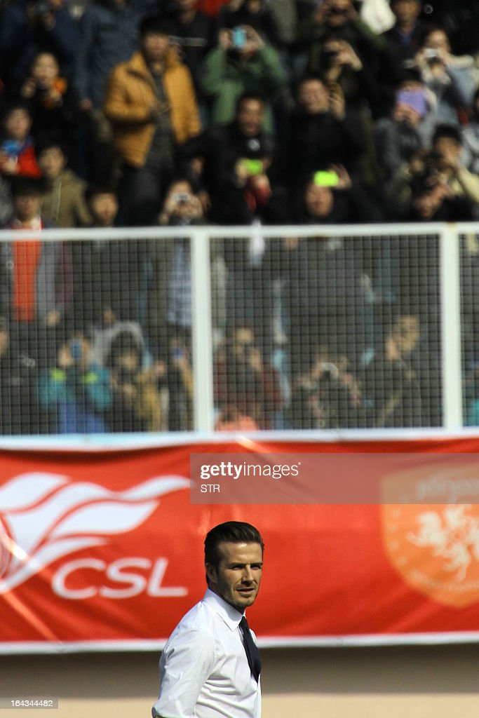 This picture taken on March 22, 2013 shows football superstar David Beckham (bottom C) playing football with young Chinese players in Tiantai Stadium in Qingdao, east China's Shandong province. Beckham raised the prospect of one last stop on his global football journey on March 20, refusing to rule out playing in China after his contract with Paris Saint-Germain ends. CHINA