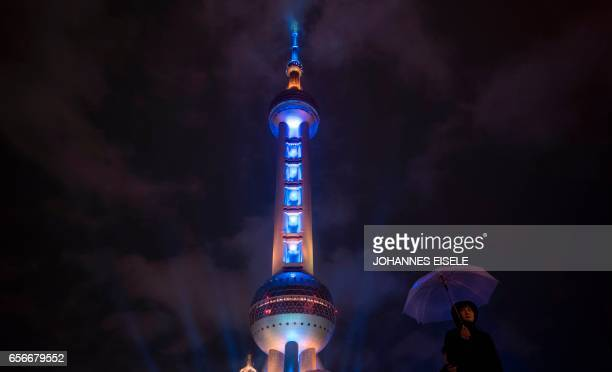 TOPSHOT This picture taken on March 22 2017 shows a woman holding an umbrella as she walks passed the Pearl Tower in Shanghai / AFP PHOTO / Johannes...