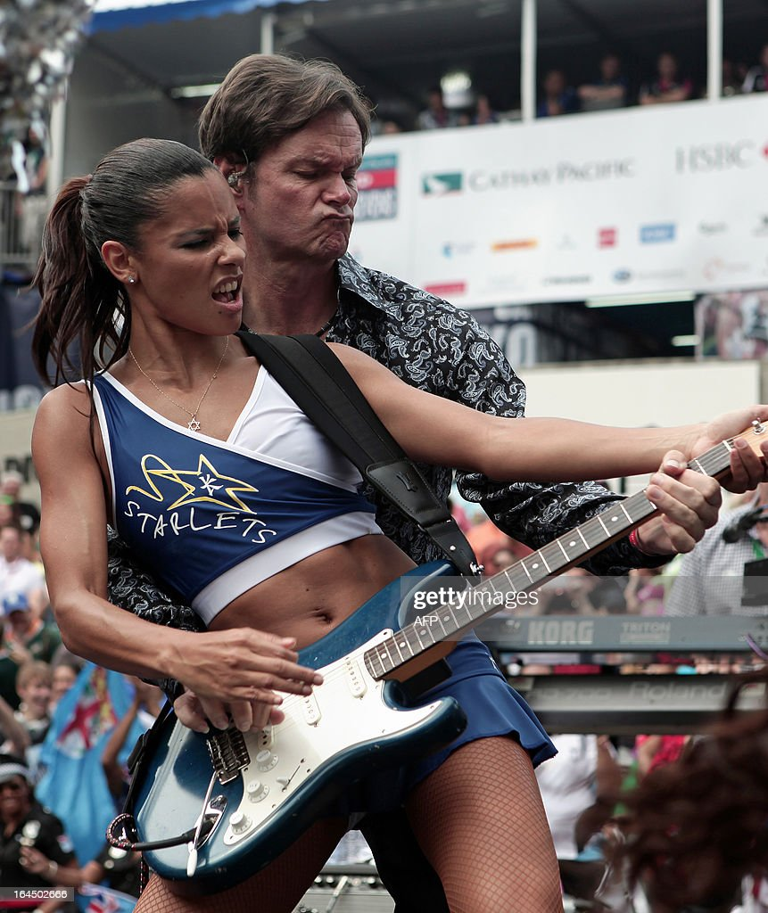 This picture taken on March 23, 2013 shows a cheerleader joining Scott Totten of the Beach Boys on stage while the band performs during a break in the action on the second day of the Hong Kong Rugby Sevens tournament.