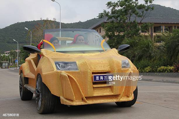 This picture taken on March 24 shows people driving a 3D printed electric car in Sanya south China's Hainan province The chassis of the concept car...