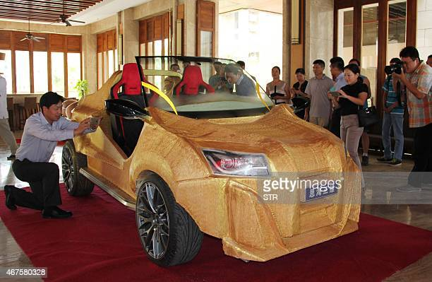 This picture taken on March 24 shows people taking photos of a 3D printed electric car in Sanya south China's Hainan province The chassis of the...