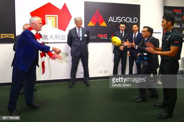 This picture taken on March 25 2017 shows Australia's Prime Minister Malcolm Turnbull passing a ball to China's Premier Li Keqiang during a visit to...
