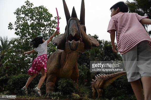 This picture taken on March 28 2016 shows children attacking a model triceratops with balloon swords at Dinosaur Planet a recentlyopened educational...