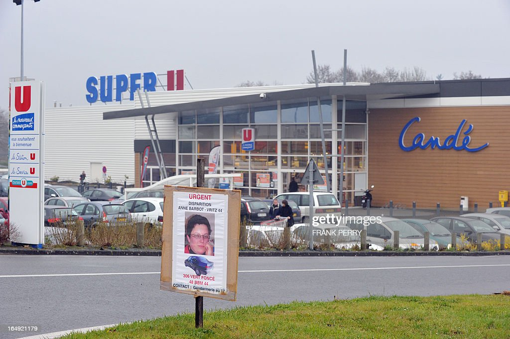 This picture taken on March 29, 2013 in Cande, northwestern France, shows a placard showing a wanted notice for Anne Barbot, aged 38, in front of the supermarket where she worked and was heading to when she disappeared two weeks ago. The dead body that was found in the boot of a burnt car in the woods of Chanveaux, northwestern France, on March 28, 2013, could be Barbot's according to the police. AFP PHOTO / FRANK PERRY