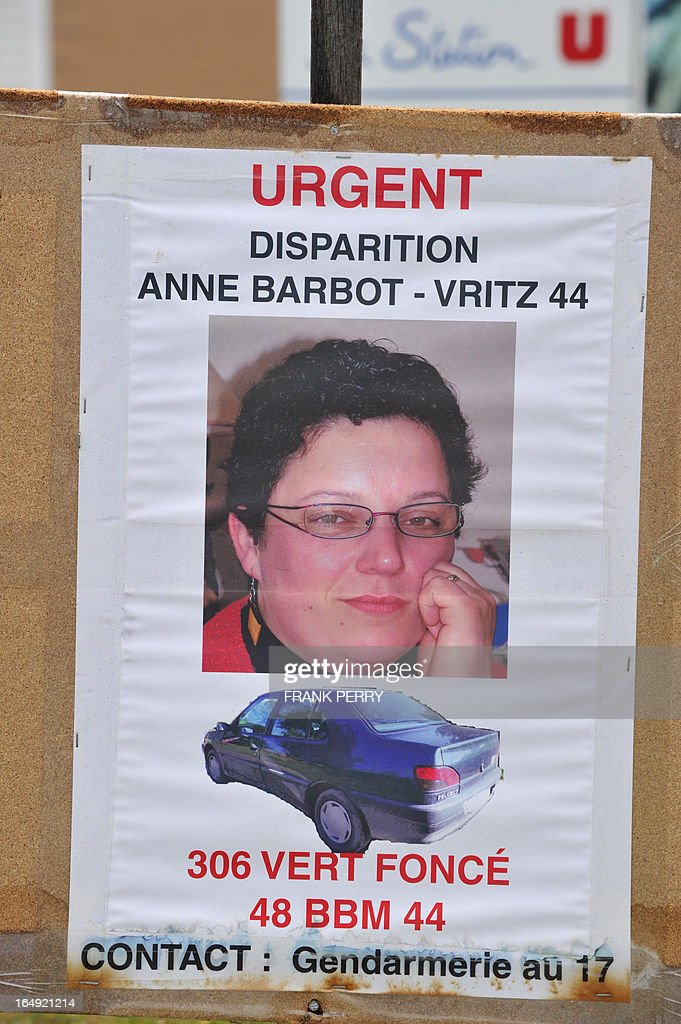 This picture taken on March 29, 2013 in Cande, northwestern France, shows a placard showing a wanted notice for Anne Barbot, aged 38, in front of the supermarket where she worked and was heading to when she disappeared two weeks ago. The dead body that was found in the boot of a burnt car in the woods of Chanveaux, northwestern France, on March 28, 2013, could be Barbot's according to the police.