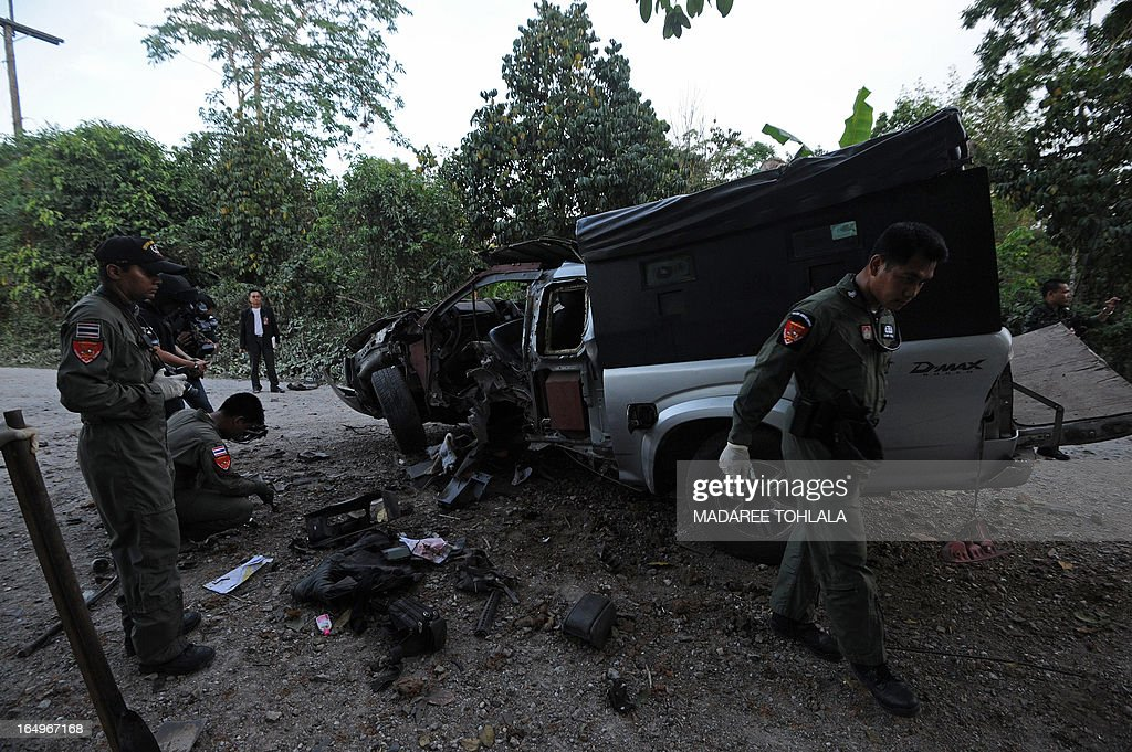 This picture taken on March 29, 2013 shows Thai bomb squad members inspecting the site of a roadside bomb attack by suspected separatist militants on a pick-up truck carrying soldiers in Thailand's restive southern province of Narathiwat. One soldiers was killed and 15 were injured in the attack. A stubborn insurgency seeking greater autonomy has raged across several provinces in the south of Thailand bordering Malaysia for nine years -- with near-daily shootings and bombings. AFP PHOTO/Madaree TOHLALA