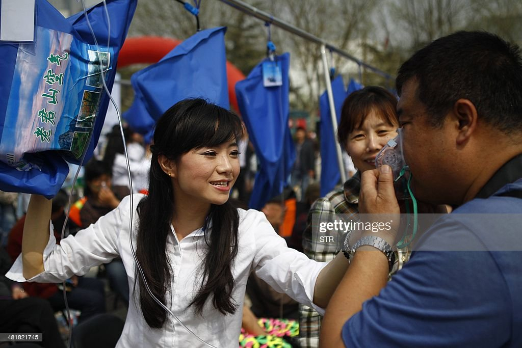 This picture taken on March 29 2014 shows a woman helping a resident try out some 'mountain air' from a blue bag in a square in Zhengzhou in central...