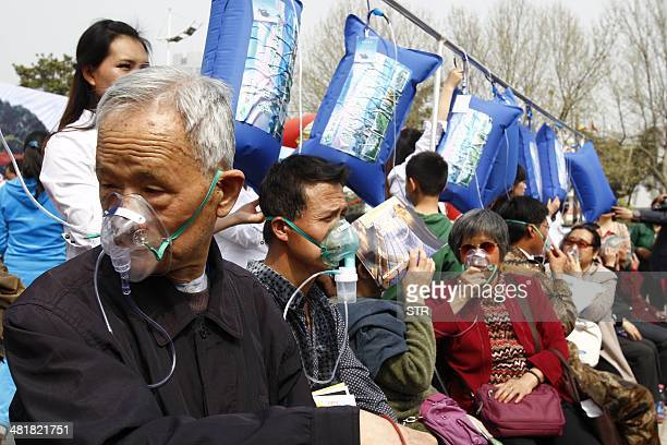 This picture taken on March 29 2014 shows residents breathing 'mountain air' from blue bags in a square in Zhengzhou in central China's Henan...