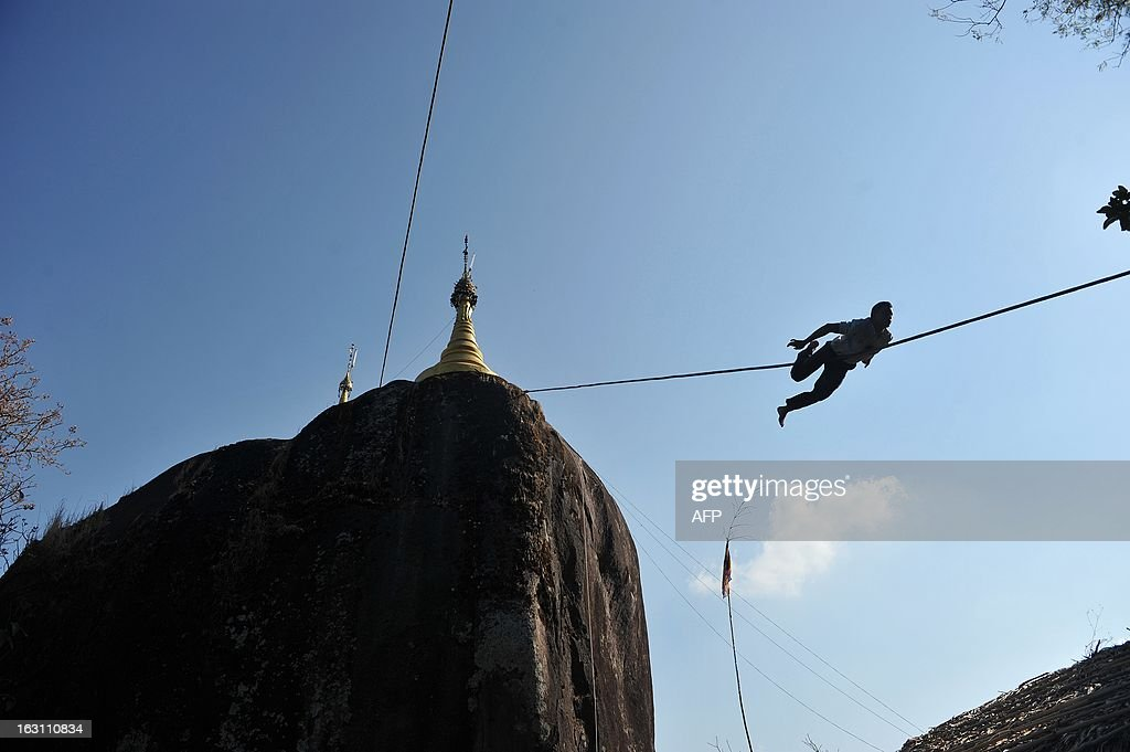 This picture taken on March 3, 2013 shows a pagoda trustee using a rope to climb down from a small pagoda after applying a gold leaf on behalf of a devotee near the Kyaikhtiyo (Golden Rock) pagoda in Myanmar's eastern Mon state. A well-known Buddhist pilgrimage site in Mon State, the Kyaikhtiyo pagoda is built on the top of a granite boulder covered with gold leaves pasted on by devotees. According to legend, the Golden Rock is perched on a strand of the Buddha's hair. AFP PHOTO / Ye Aung THU