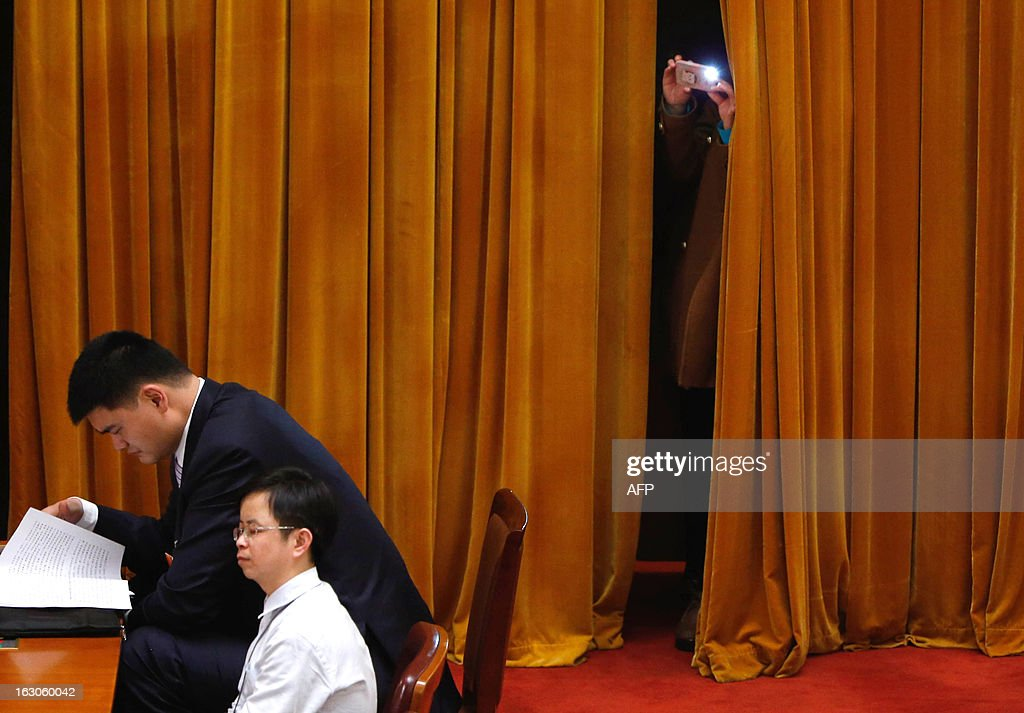 This picture taken on March 3, 2013 shows a woman taking a picture behind retired Chinese professional basketball player Yao Ming (L) on the opening session of the Chinese People's Political Consultative Conference (CPPCC) at the Great Hall of the People in Beijing. Thousands of delegates from across China meet this week to seal a power transfer to new leaders whose first months running the Communist Party have pumped up expectations with a deluge of propaganda. CHINA